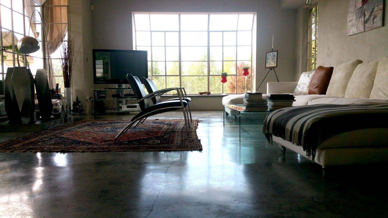 הסלון המואר עם רצפת הבטון המוחלק בבית למכירה בבנין ציון